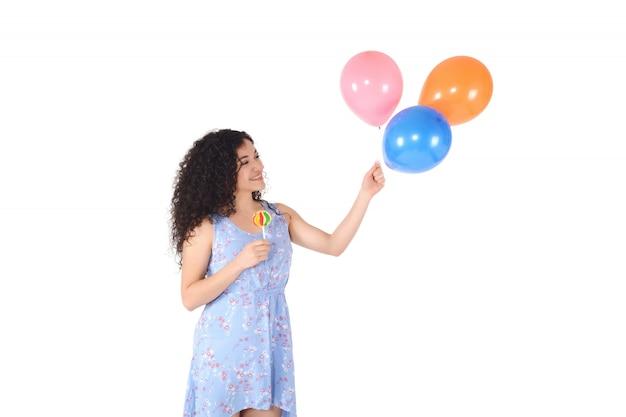 Belle femme avec une sucette sucrée et des ballons. Photo Premium