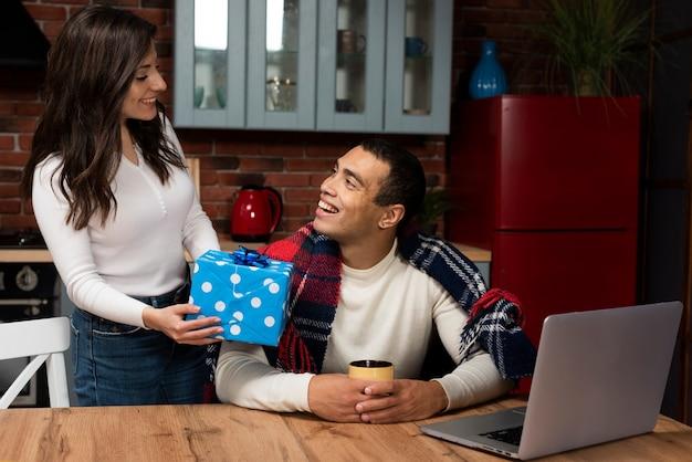 Belle femme surprenant homme avec un cadeau Photo gratuit
