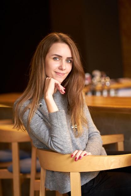 Belle Femme Sympathique Et Gaie Aux Cheveux Longs Portant Un Pull Gris Situé Sur La Chaise Et Souriant. Photo Premium