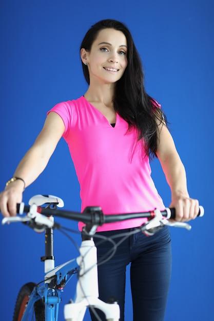 Belle Femme En T-shirt Rose Sourire Et Tenir Le Vélo Derrière Le Volant. Photo Premium
