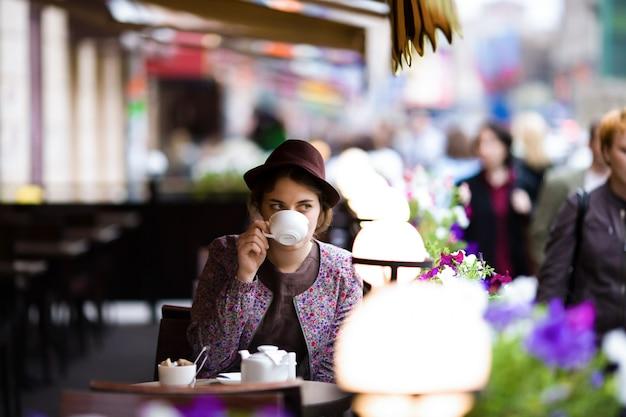 Belle femme avec une tasse de thé assis dans un café. Photo Premium