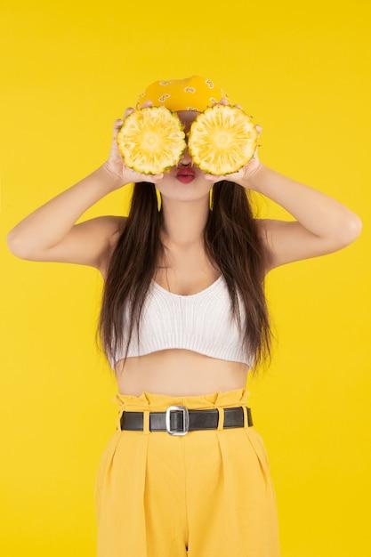 Belle femme tenant un ananas Photo gratuit