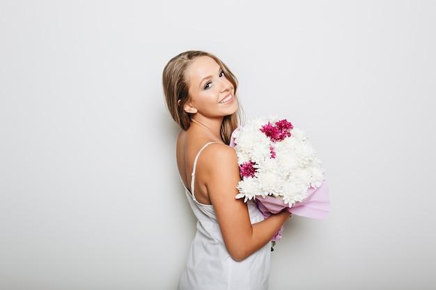 Belle femme tenant un bouquet de fleurs Photo gratuit
