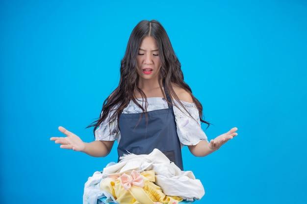 Une belle femme tenant un chiffon prêt à laver sur bleu Photo gratuit