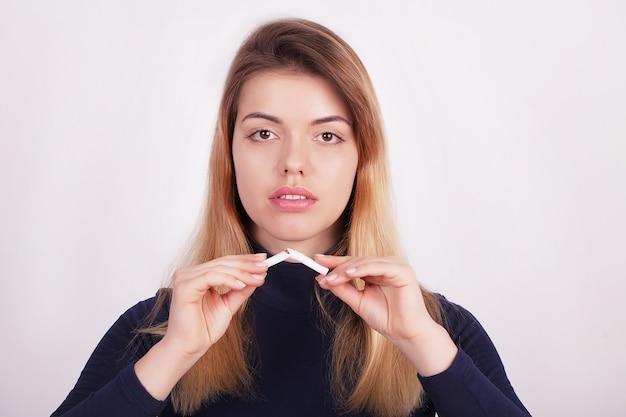 Belle Femme Tenant Une Cigarette Cassée. Arrêter De Fumer Photo Premium