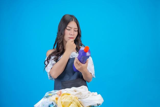 Belle femme tenant un détergent à lessive préparé sur bleu Photo gratuit