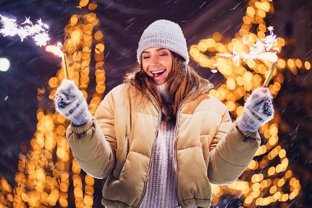 Belle femme tenant des étincelles et s'amuser en plein air Photo Premium