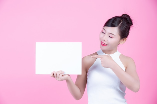 Belle femme tenant une feuille de tableau blanc sur un fond rose. Photo gratuit