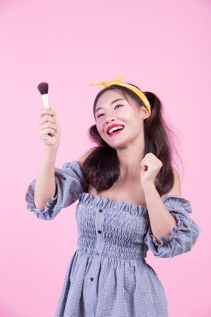 Belle femme tenant un pinceau, brossé sur un fond rose. Photo gratuit