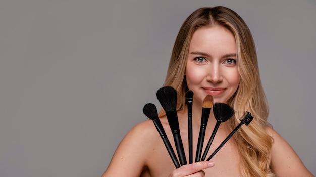Belle Femme Tenant Des Pinceaux De Maquillage Photo gratuit