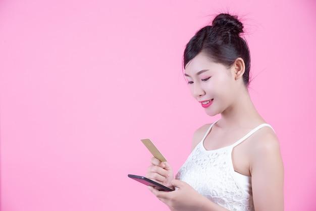 Belle femme tenant un smartphone et une carte sur un fond rose Photo gratuit