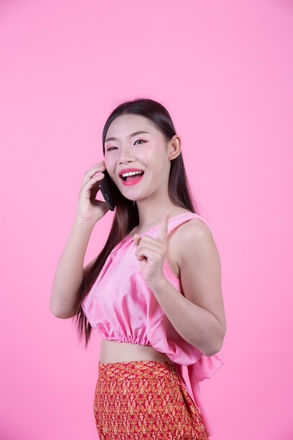 Belle femme tenant un smartphone sur un fond rose. Photo gratuit