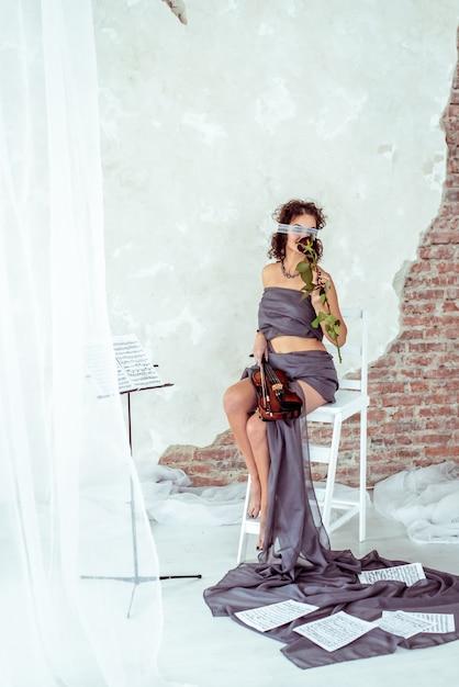 Belle femme tenant un violon et sentant la rose rouge Photo Premium