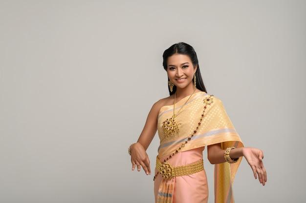 Belle femme thaïlandaise vêtue d'une robe thaïlandaise et danse thaïlandaise Photo gratuit