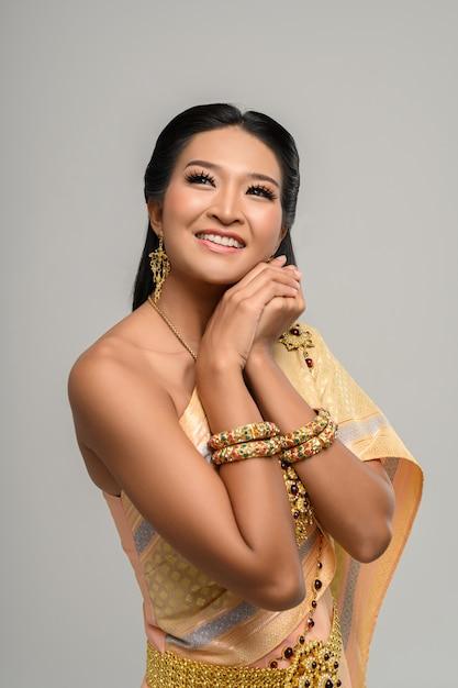 Belle femme thaïlandaise vêtue d'une robe thaïlandaise et d'un sourire heureux. Photo gratuit