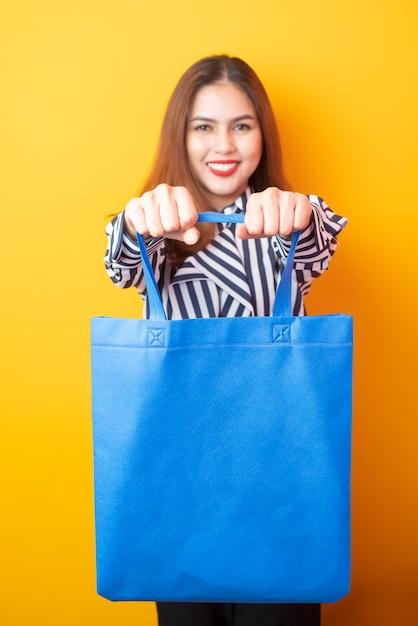 Belle femme tient un sac en tissu bleu Photo Premium
