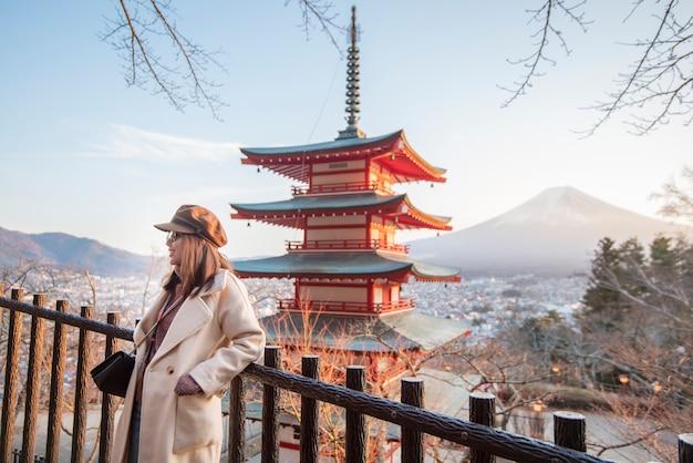Belle femme touriste souriant sur la pagode chureito et la montagne fuji, japon Photo Premium