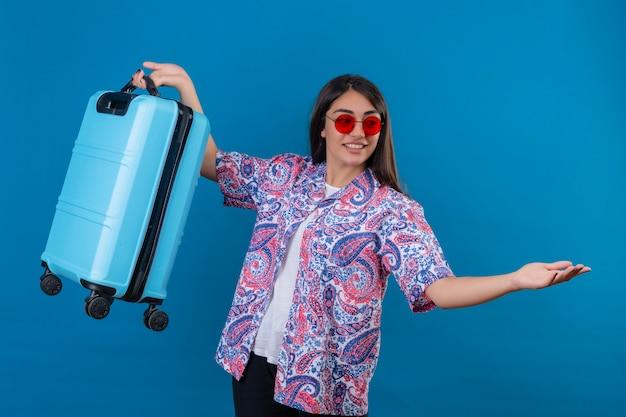 Belle Femme Touristique Portant Des Lunettes De Soleil Rouges Tenant Une Valise De Voyage Souriant Sympathique Debout Avec Les Bras En Signe De Bienvenue Sur L'espace Bleu Isolé Photo gratuit