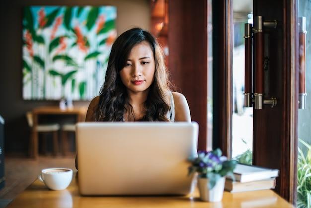Belle femme travaillant avec un ordinateur portable au café café Photo gratuit
