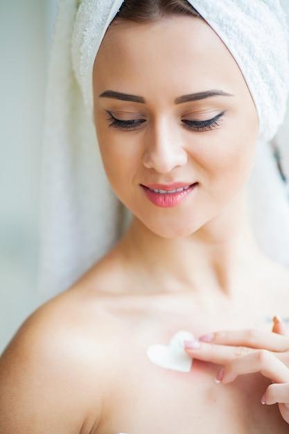 Une belle femme utilisant un produit de soin de la peau, une crème hydratante ou une lotion et skincare prenant soin de son teint sec. crème hydratante aux mains féminines Photo Premium