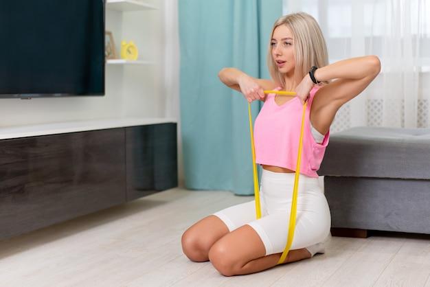 Belle Femme En Vêtements Sportifs De Mode Faisant Exercer Avec Une Bande Jaune à La Maison. Séances D'entraînement à Domicile Photo Premium