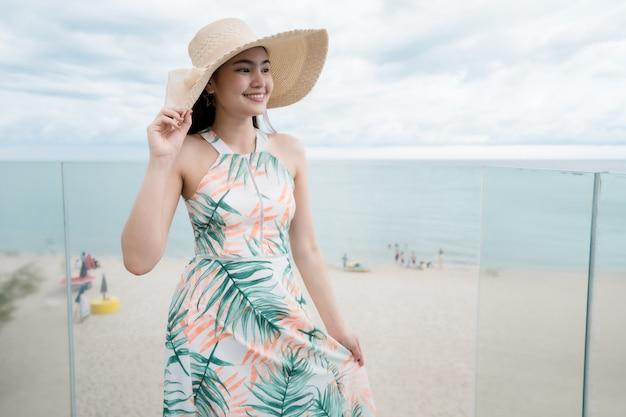 Belle femme vêtue d'une belle robe marchant sur les vacances d'été d'escaliers en verre. Photo Premium