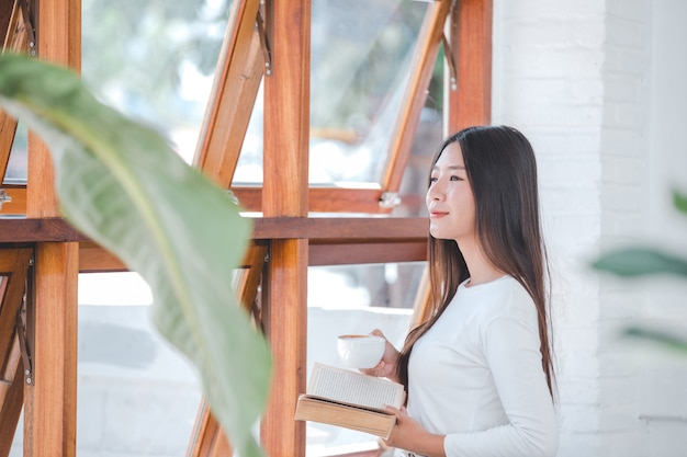 Une belle femme vêtue d'une chemise blanche à manches longues assis dans un café Photo gratuit