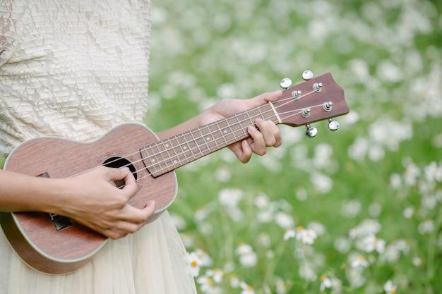 Belle femme vêtue d'une jolie robe blanche et tenant un ukulélé Photo gratuit