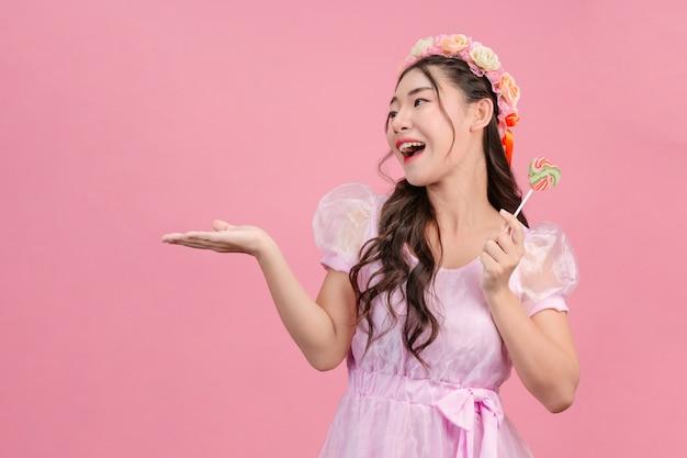 Une belle femme vêtue d'une princesse rose joue avec son bonbon sucré sur un rose. Photo gratuit