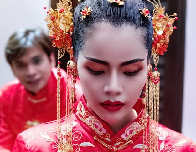 La Belle Femme Vêtue D'une Robe Rouge, Debout Devant Un Bel Homme Flou, Portrait De Modèle Posant, Festival Du Nouvel An Chinois, Effet De Lumière Parasite, Lumière Floue Arund Photo Premium