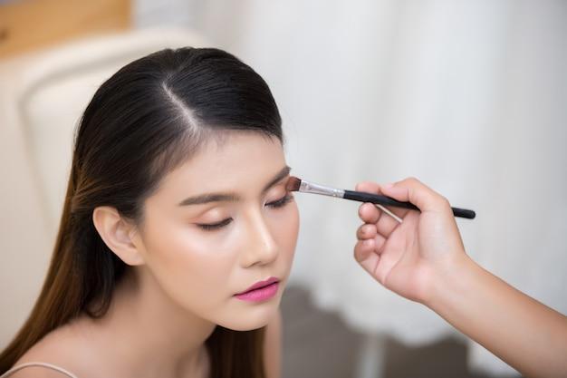 Belle femme visage et main de maquillage Photo gratuit