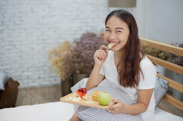 Belle Femme Yong Heureuse Manger Le Petit Déjeuner Avec Des Fruits Et Des Gâteaux Sur Le Lit Photo Premium