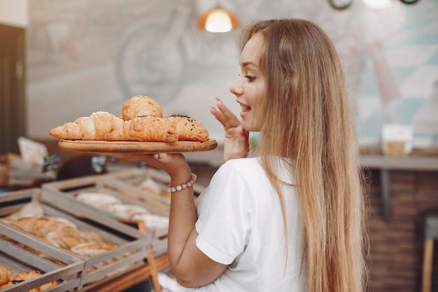 Belle fille achète des petits pains à la boulangerie Photo gratuit