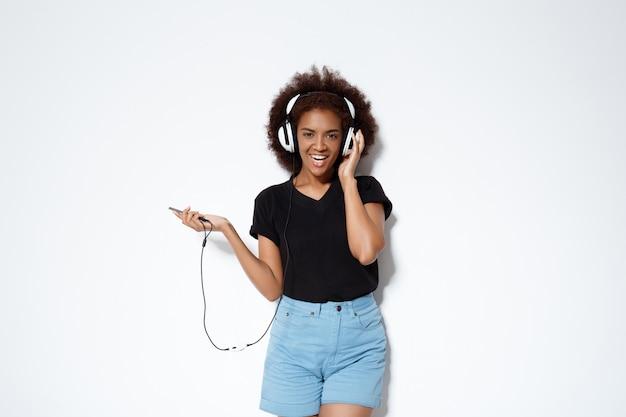 Belle Fille Africaine, écouter De La Musique Dans Les écouteurs Sur Le Mur Blanc. Photo gratuit