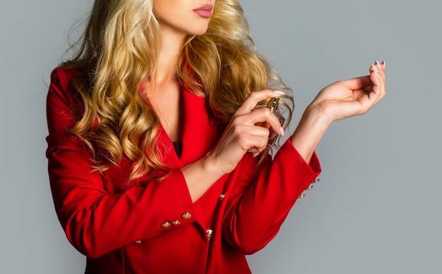 Belle Fille à L'aide De Parfum. Femme Avec Une Bouteille De Parfum. Flacon De Parfum Femme Arôme De Pulvérisation. Femme Tenant Une Bouteille De Parfums. Femme Présente Des Parfums Parfumés. Photo Premium