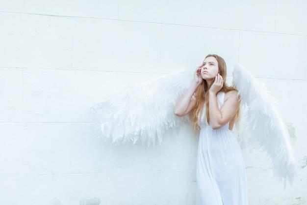 Belle Fille Ange Aux Ailes Blanches Près Du Mur Regardant Pensivement Photo Premium