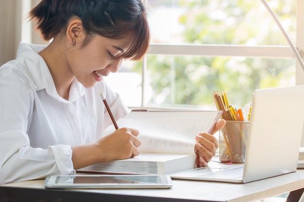 Belle fille asiatique d'apprentissage et d'écriture en manuel ou à la maison Photo Premium
