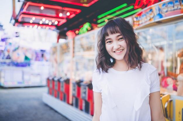 Belle fille asiatique dans un parc d'attractions, souriant Photo Premium