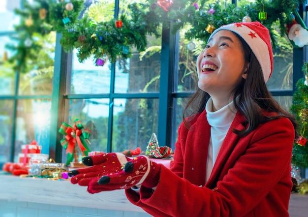 Belle fille asiatique à noël portant et bonnet de noel, avec deux mains tenant ou offrant quelque chose Photo Premium