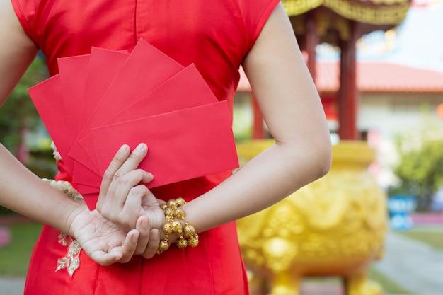 Une belle fille asiatique vêtue d'une robe rouge Photo gratuit