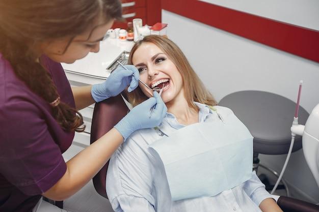 Belle fille assise dans le bureau du dentiste Photo gratuit
