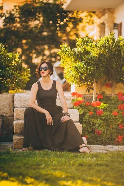 Belle fille assise dans les escaliers dans le parc Photo Premium