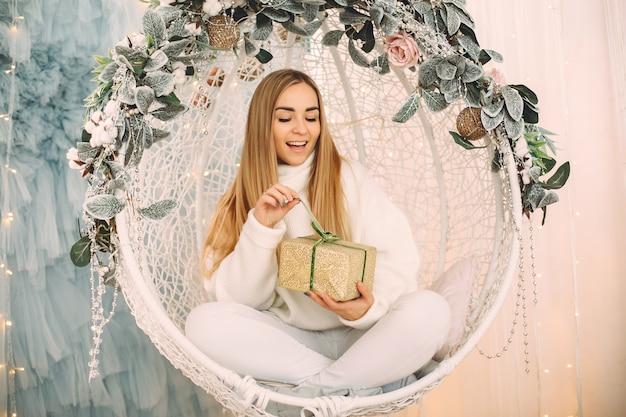 Belle Fille Assise Dans Un Studio Avec Des Cadeaux Photo gratuit