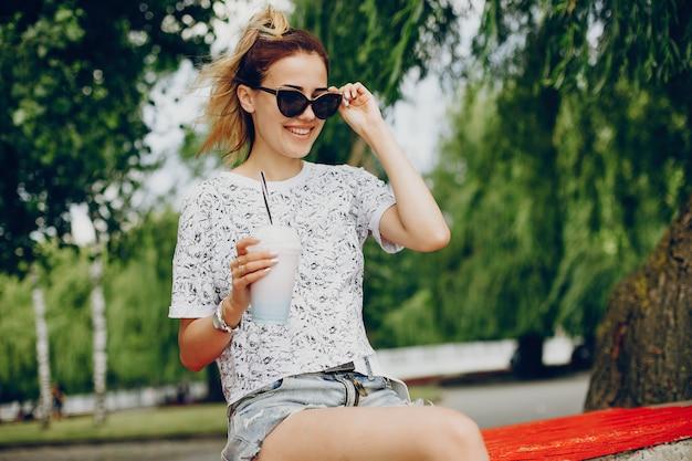 Belle fille assise sur le front de mer Photo gratuit