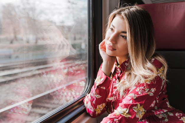 Belle fille assise seule dans un train et regarde tristement par la fenêtre Photo Premium