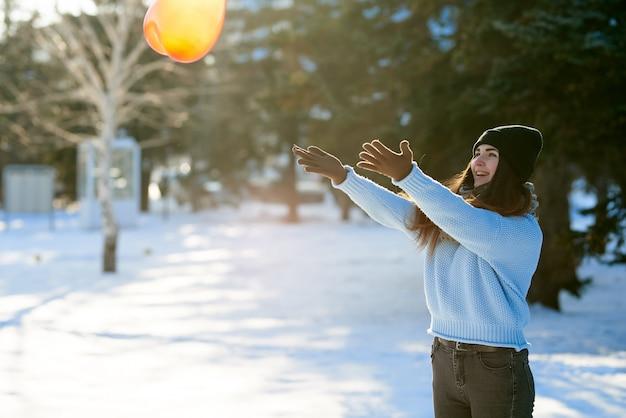 Belle fille attrape un ballon en forme de coeur, saint valentin Photo Premium