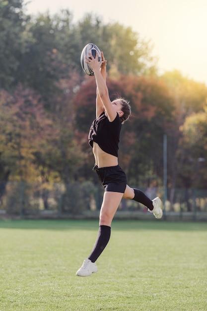 Belle fille attraper un ballon de rugby Photo gratuit