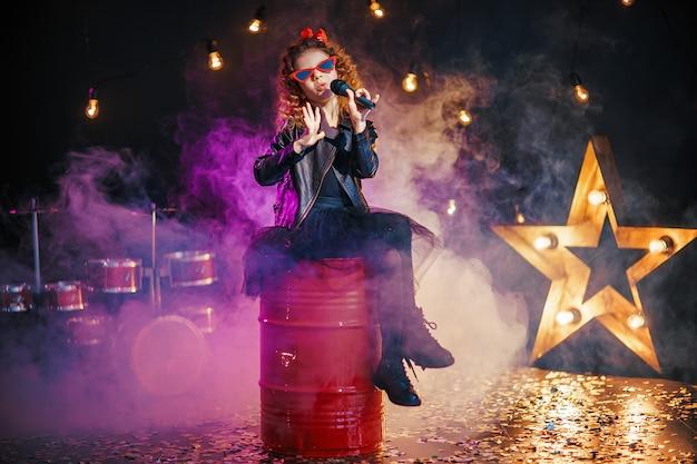 Belle Fille Aux Cheveux Bouclés Portant Une Veste En Cuir Et Des Lunettes De Soleil Rouges Chante Dans Un Microphone Sans Fil Photo Premium