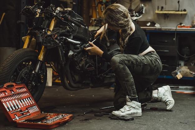 Belle fille aux cheveux longs dans le garage réparer une moto Photo gratuit