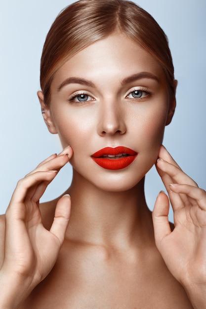 Belle fille aux lèvres rouges et maquillage classique, visage beauté Photo Premium